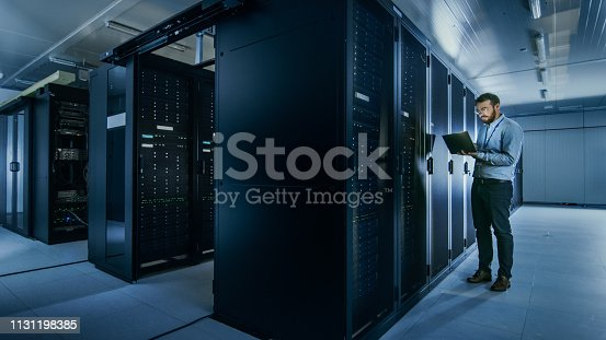 1131208605 istock photo Bearded IT Specialist in Glasses is Working on Laptop in Data Center while Standing Before Server Rack. Running Diagnostics or Doing Maintenance Work. 1131198385