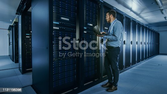 1131198396istockphoto Bearded IT Specialist in Glasses is Working on Laptop in Data Center while Standing Before Server Rack. Running Diagnostics or Doing Maintenance Work. 1131198398