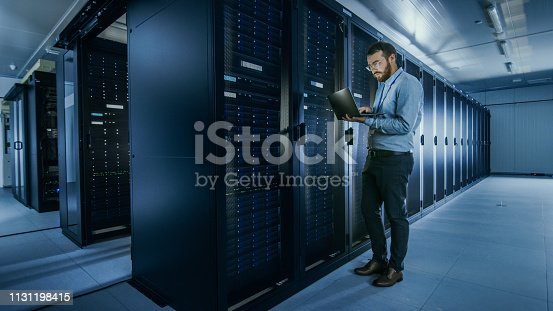 1131208605 istock photo Bearded IT Specialist in Glasses is Working on Laptop in Data Center while Standing Before Server Rack. Running Diagnostics or Doing Maintenance Work. 1131198415