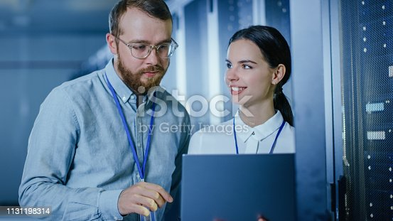 1131198396istockphoto Bearded IT Technician in Glasses and Beautiful Young Engineer Colleague with a Laptop Computer are Talking in Data Center while Working Next to Server Racks. Running Diagnostics or Doing Maintenance Work. 1131198314