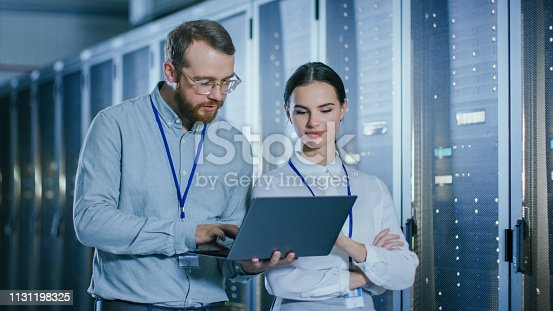 1131198396istockphoto Bearded IT Technician in Glasses and Beautiful Young Engineer Colleague with a Laptop Computer are Talking in Data Center while Working Next to Server Racks. Running Diagnostics or Doing Maintenance Work. 1131198325