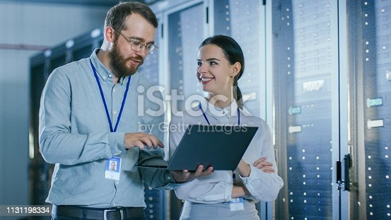 1131198396istockphoto Bearded IT Technician in Glasses and Beautiful Young Engineer Colleague with a Laptop Computer are Talking in Data Center while Working Next to Server Racks. Running Diagnostics or Doing Maintenance Work. 1131198334
