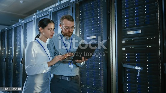 1131198396istockphoto Bearded IT Technician in Glasses with a Laptop Computer and Beautiful Young Engineer Colleague are Talking in Data Center while Working Next to Server Racks. Running Diagnostics or Doing Maintenance Work. 1131198315