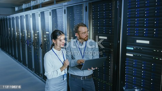 1131198396istockphoto Bearded IT Technician in Glasses with a Laptop Computer and Beautiful Young Engineer Colleague are Talking in Data Center while Working Next to Server Racks. Running Diagnostics or Doing Maintenance Work. 1131198316