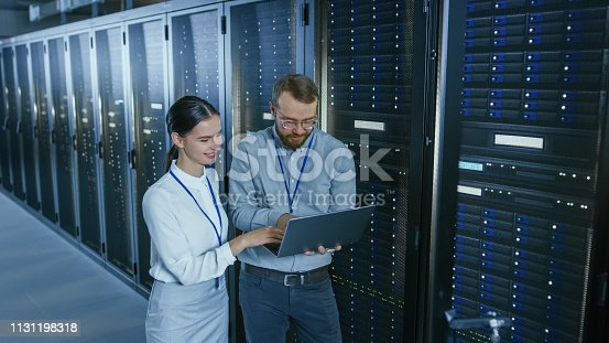 1131198396istockphoto Bearded IT Technician in Glasses with a Laptop Computer and Beautiful Young Engineer Colleague are Talking in Data Center while Working Next to Server Racks. Running Diagnostics or Doing Maintenance Work. 1131198318