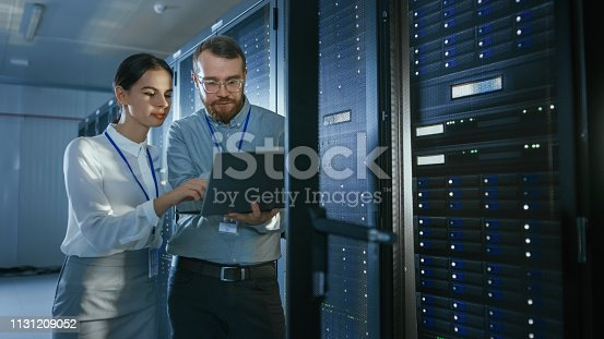 1131208605 istock photo Bearded IT Technician in Glasses with a Laptop Computer and Beautiful Young Engineer Colleague are Talking in Data Center while Working Next to Server Racks. Running Diagnostics or Doing Maintenance Work. 1131209052