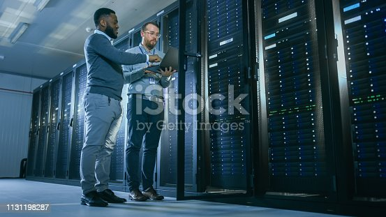 1131198396 istock photo Bearded IT Technician in Glasses with a Laptop Computer and Black Male Engineer Colleague are Talking in Data Center while Working Next to Server Racks. Running Diagnostics or Doing Maintenance Work. 1131198287