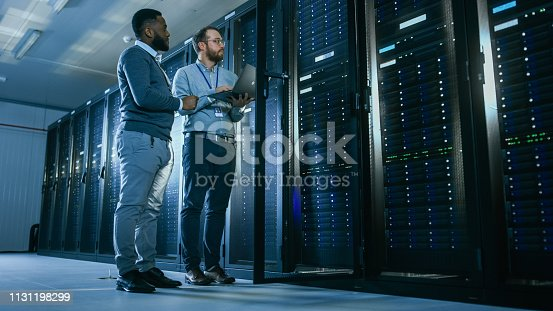 1131198396istockphoto Bearded IT Technician in Glasses with a Laptop Computer and Black Male Engineer Colleague are Talking in Data Center while Working Next to Server Racks. Running Diagnostics or Doing Maintenance Work. 1131198299