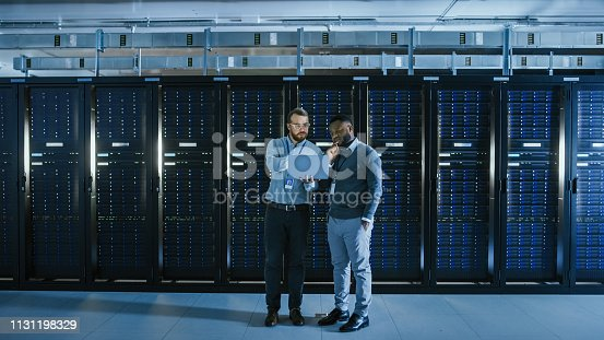 1131208605istockphoto Bearded IT Technician in Glasses with a Laptop Computer and Black Male Engineer Colleague Have Discussion in Data Center while Working Next to Server Racks. Running Diagnostics or Doing Maintenance Work. 1131198329