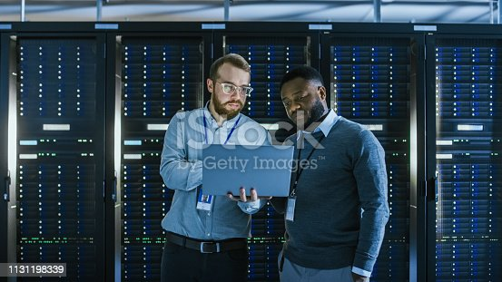 1131208605istockphoto Bearded IT Technician in Glasses with a Laptop Computer and Black Male Engineer Colleague are Talking in Data Center while Working Next to Server Racks. Running Diagnostics or Doing Maintenance Work. 1131198339
