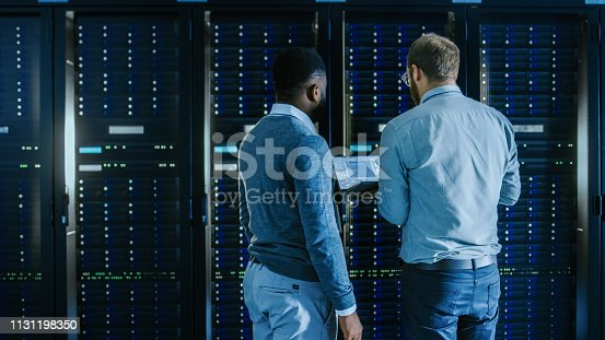 1131198396 istock photo Bearded IT Technician in Glasses with a Laptop Computer and Black Male Engineer Colleague are Working in Data Center while Working Next to Server Racks. Running Diagnostics or Doing Maintenance Work. 1131198350
