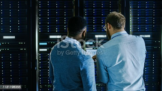 1131198396 istock photo Bearded IT Technician in Glasses with a Laptop Computer and Black Male Engineer Colleague are Talking in Data Center while Working Next to Server Racks. Running Diagnostics or Doing Maintenance Work. 1131198355