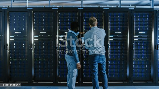 1131198396istockphoto Bearded IT Technician in Glasses with a Laptop Computer and Black Male Engineer Colleague are Talking in Data Center while Working Next to Server Racks. Running Diagnostics or Doing Maintenance Work. 1131198357
