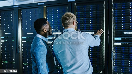 1131198396istockphoto Bearded IT Technician in Glasses with a Laptop Computer and Black Male Engineer Colleague are Talking in Data Center while Working Next to Server Racks. Running Diagnostics or Doing Maintenance Work. 1131198362