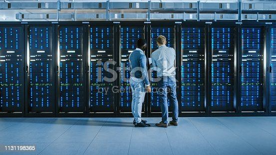 1131198396istockphoto Bearded IT Technician in Glasses with a Laptop Computer and Black Male Engineer Colleague are Talking in Data Center while Working Next to Server Racks. Running Diagnostics or Doing Maintenance Work. 1131198365