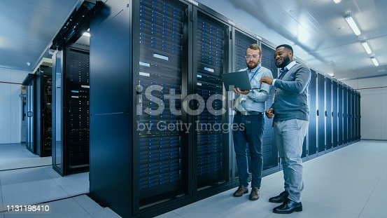 1131208605 istock photo Bearded IT Technician in Glasses with a Laptop Computer and Black Male Engineer Colleague are Talking in Data Center while Working Next to Server Racks. Running Diagnostics or Doing Maintenance Work. 1131198410
