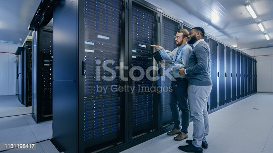 1131208605 istock photo Bearded IT Technician in Glasses with a Laptop Computer and Black Male Engineer Colleague are Talking in Data Center while Working Next to Server Racks. Running Diagnostics or Doing Maintenance Work. 1131198417