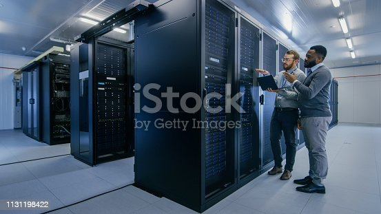 1131208605 istock photo Bearded IT Technician in Glasses with a Laptop Computer and Black Male Engineer Colleague are Talking in Data Center while Working Next to Server Racks. Running Diagnostics or Doing Maintenance Work. 1131198422
