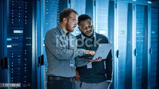 1131208605 istock photo Bearded IT Technician in Glasses with Laptop Computer and Black Male Engineer Colleague are Using Laptop in Data Center while Working Next to Server Racks. Running Diagnostics or Doing Maintenance Work 1131198162