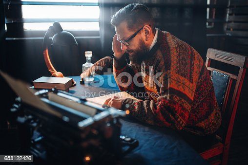 655113470 istock photo Bearded journalist in glasses reading his work 658122426