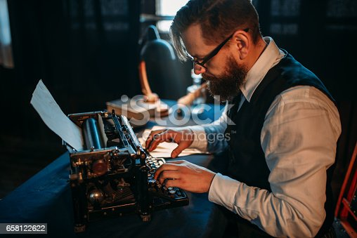 655113470 istock photo Bearded journalist in glasses typing on typewriter 658122622