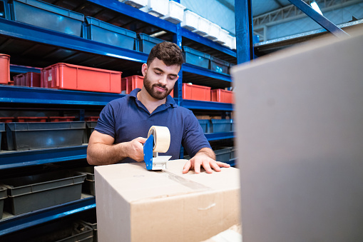 Bearded Laborer Closing Cardboard Box For Shipping Stock Photo - Download Image Now