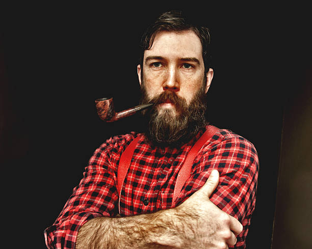 Bearded lumberjack man with pipe and suspenders A man dressed as a lumberjack with a plaid shirt and suspenders has a big beard and a pipe in his mouth. lumberjack stock pictures, royalty-free photos & images