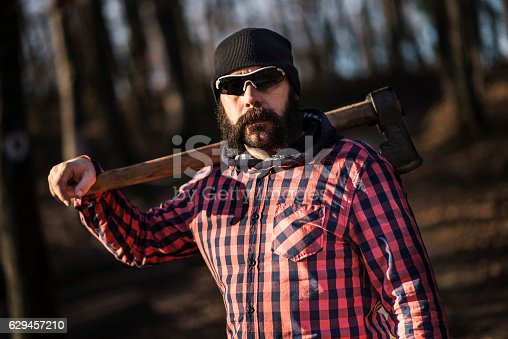 Bearded lumberjack worker standing in the forest with axe