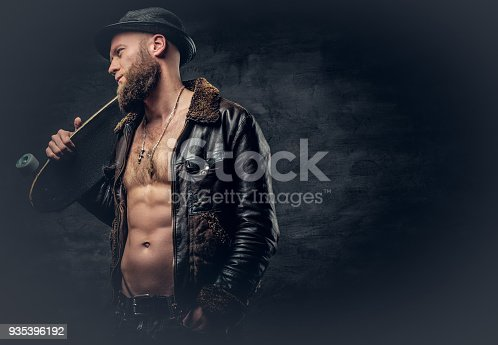 istock Bearded male dressed in leather jackett holds skateboard. 935396192
