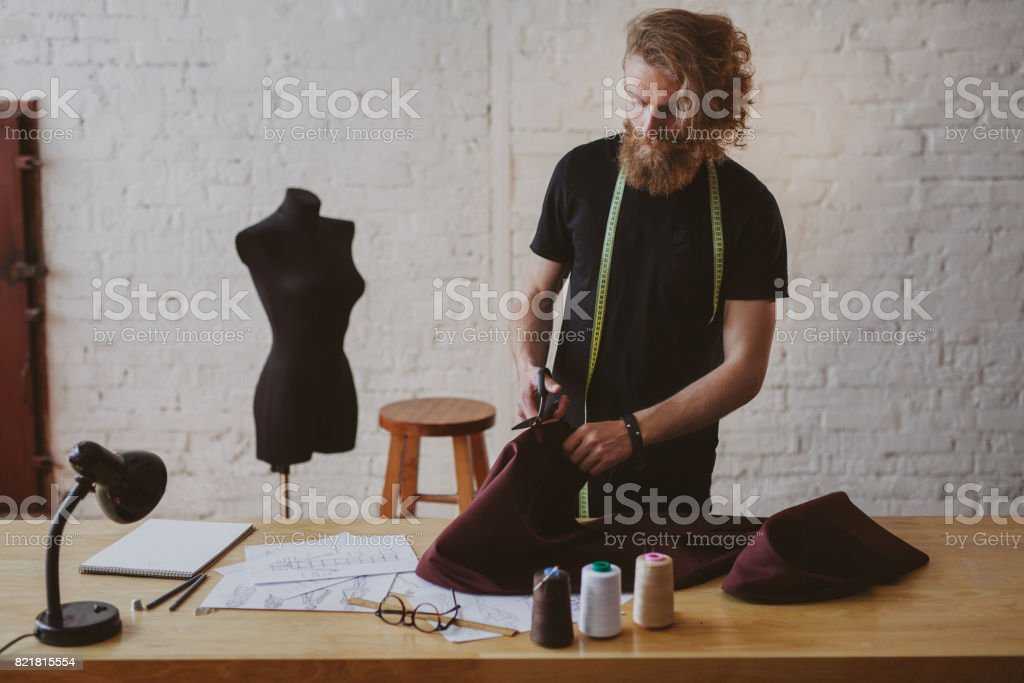 Bearded male dressmaker snipping cloth stock photo
