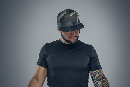 Bearded male in a baseball cap looking.