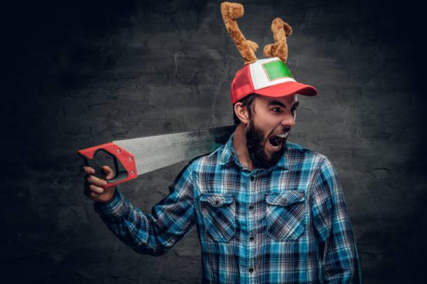 ein bärtiger mann mit hut mit hörnern hirsche hält handsäge. - waldhandwerk stock-fotos und bilder