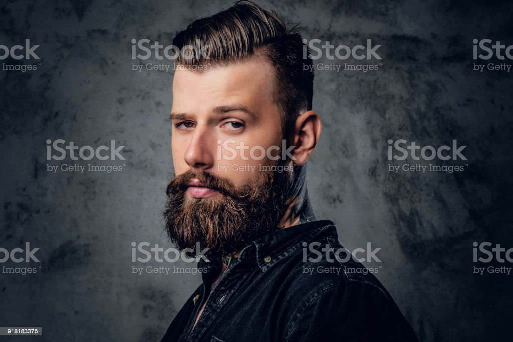Homme barbu dans une chemise noire avec tatouage sur son cou. - Photo