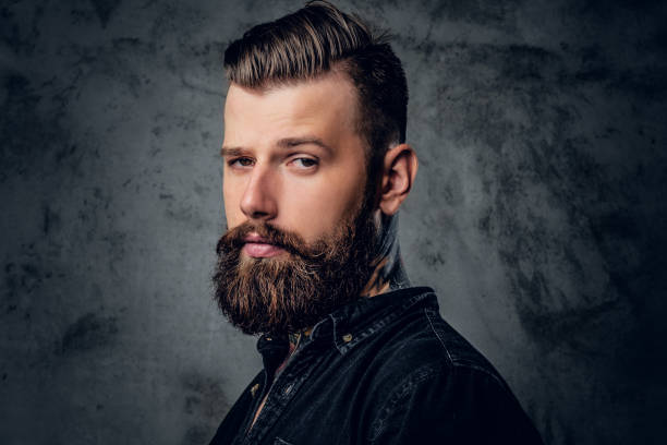 Bearded male in black shirt with tattoo on his neck. stock photo
