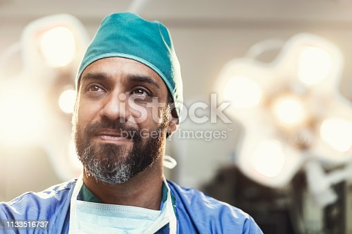 Bearded male surgeon looking away. Doctor is working in illuminated operating room. He is wearing scrubs.