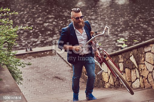 istock A bearded male with a haircut dressed in casual clothes and sunglasses, climbs the stairs, trying to hide from the rain. 1026141816