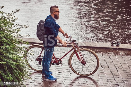 istock A bearded male with a haircut dressed in casual clothes and sunglasses, standing in the rain, in a park. 1026144344