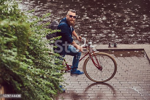 istock A bearded male with a haircut dressed in casual clothes and sunglasses, standing in the rain, in a park. 1026144436