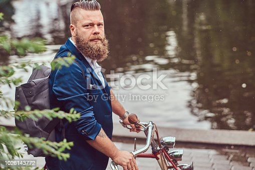 istock Bearded male with a stylish haircut dressed in casual clothes with a backpack, standing with a retro bicycle near the river in a city park. 1026143772