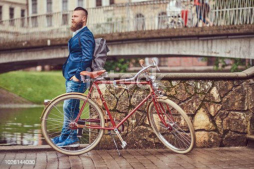 istock Bearded male with a stylish haircut dressed in casual clothes with a backpack, standing with a retro bicycle near the river in a city park. 1026144030