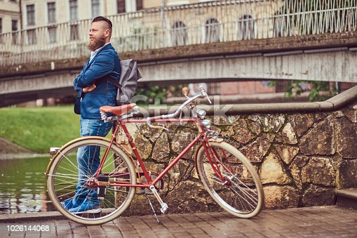 istock Bearded male with a stylish haircut dressed in casual clothes with a backpack, standing with a retro bicycle near the river in a city park. 1026144068