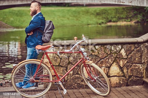 istock Bearded male with a stylish haircut dressed in casual clothes with a backpack, standing with a retro bicycle near the river in a city park. 1026144122
