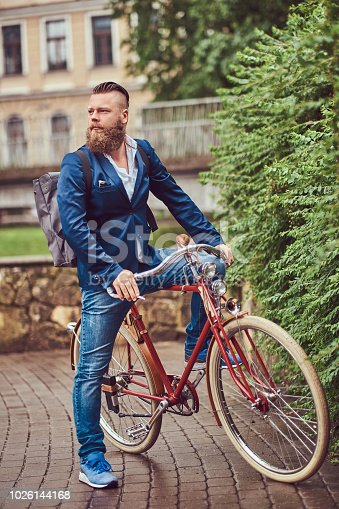istock A bearded male with a stylish haircut dressed in casual clothes with a backpack, sitting on a retro bicycle in a city park. 1026144168