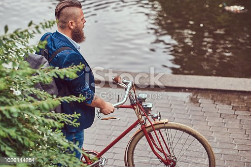 istock Bearded male with a stylish haircut dressed in casual clothes with a backpack, standing with a retro bicycle near the river in a city park. 1026144284