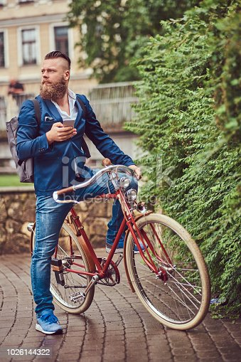 istock A bearded male with a stylish haircut dressed in casual clothes with a backpack, sitting on a retro bicycle in a city park. 1026144322