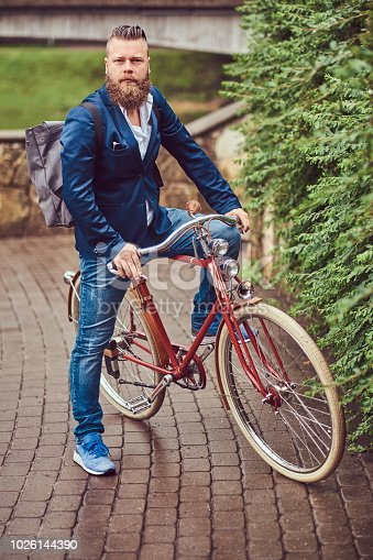 istock A bearded male with a stylish haircut dressed in casual clothes with a backpack, sitting on a retro bicycle in a city park. 1026144390