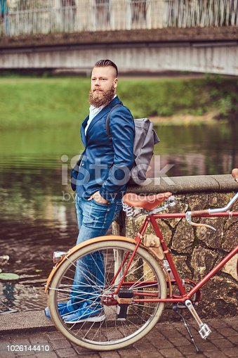 istock Bearded male with a stylish haircut dressed in casual clothes with a backpack, standing with a retro bicycle near the river in a city park. 1026144410