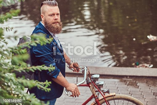 istock Bearded male with a stylish haircut dressed in casual clothes with a backpack, standing with a retro bicycle near the river in a city park. 1026144482