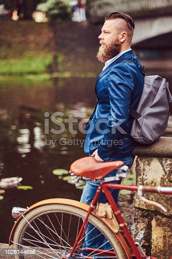 istock Bearded male with a stylish haircut dressed in casual clothes with a backpack, standing with a retro bicycle near the river in a city park. 1026144698