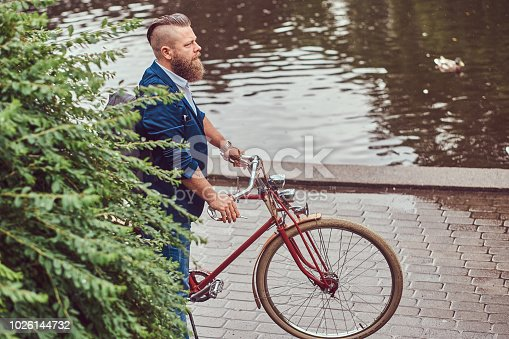 istock Bearded male with a stylish haircut dressed in casual clothes with a backpack, standing with a retro bicycle near the river in a city park. 1026144732